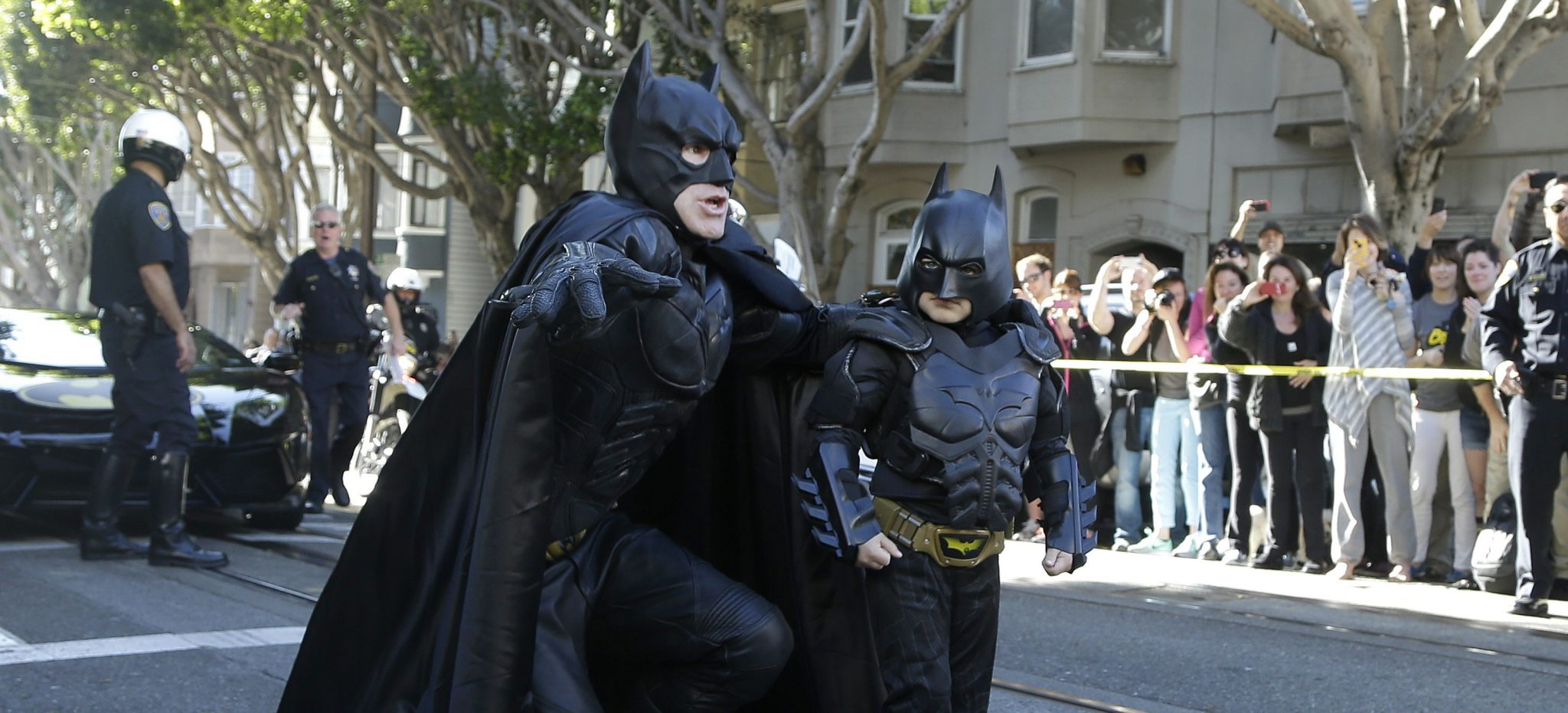 """Miles Scott, dressed as Batkid, right, walks with Batman before saving a damsel in distress in San Francisco, Friday, Nov. 15, 2013.  San Francisco turned into Gotham City on Friday, as city officials helped fulfill Scott's wish to be """"Batkid.""""Scott, a leukemia patient from Tulelake in far Northern California, was called into service on Friday morning by San Francisco Police Chief Greg Suhr to help fight crime, The Greater Bay Area Make-A-Wish Foundation says. (AP Photo/Jeff Chiu)"""
