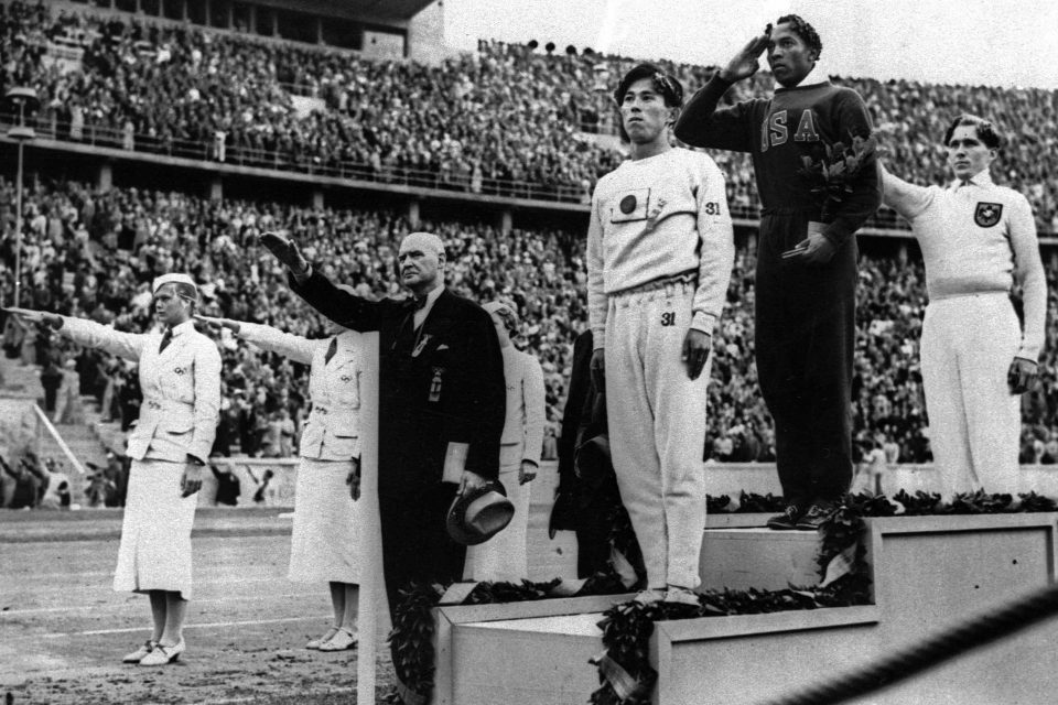 """FILE - In this Aug. 11, 1936 file photo, Olympic broad jump medalists salute during the medals ceremony at the Summer Olympics in Berlin. From left on podium are: bronze medalist Jajima of Japan, gold medalist Jesse Owens of the United States and silver medalist Lutz Long of Germany.  Long and German Olympic officials give the Nazi salute, while Owens gives a traditional salute. It is """"difficult"""" for IOC President Thomas Bach to accept that a gold medal won by Jesse Owens at the 1936 Olympics will go on auction and possibly be bought by a private collector. The medal, one of four golds that Owens won at the Berlin Games in front of Adolf Hitler, is """"a part of world heritage,"""" Bach said Wednesday, Nov. 13, 2013. (AP Photo/File)"""
