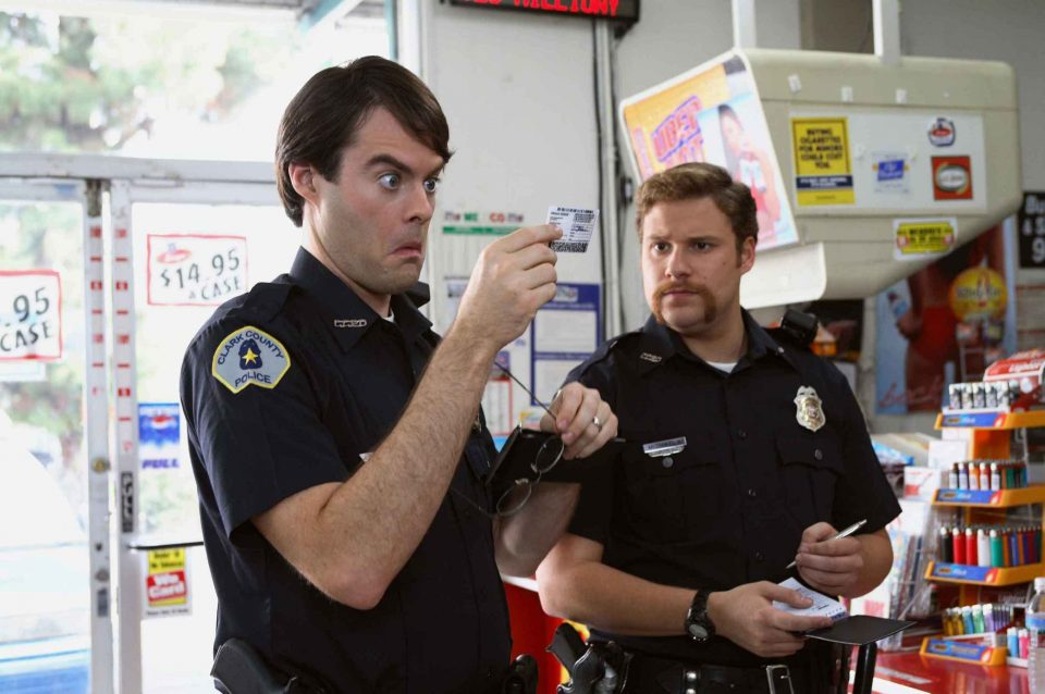 SB-242 : Two clueless cops, Officer Slater (Bill Hader, left) and Officer Michaels (Seth Rogen, right) check out the identification of McLovin, the 25-year-old Hawaiian organ donor, in Superbad, the new film from producers Judd Apatow and Shauna Robertson (The 40-Year-Old Virgin), screenwriters Seth Rogen & Evan Goldberg, and director Greg Mottola. Photo Credit : Melissa Moseley.