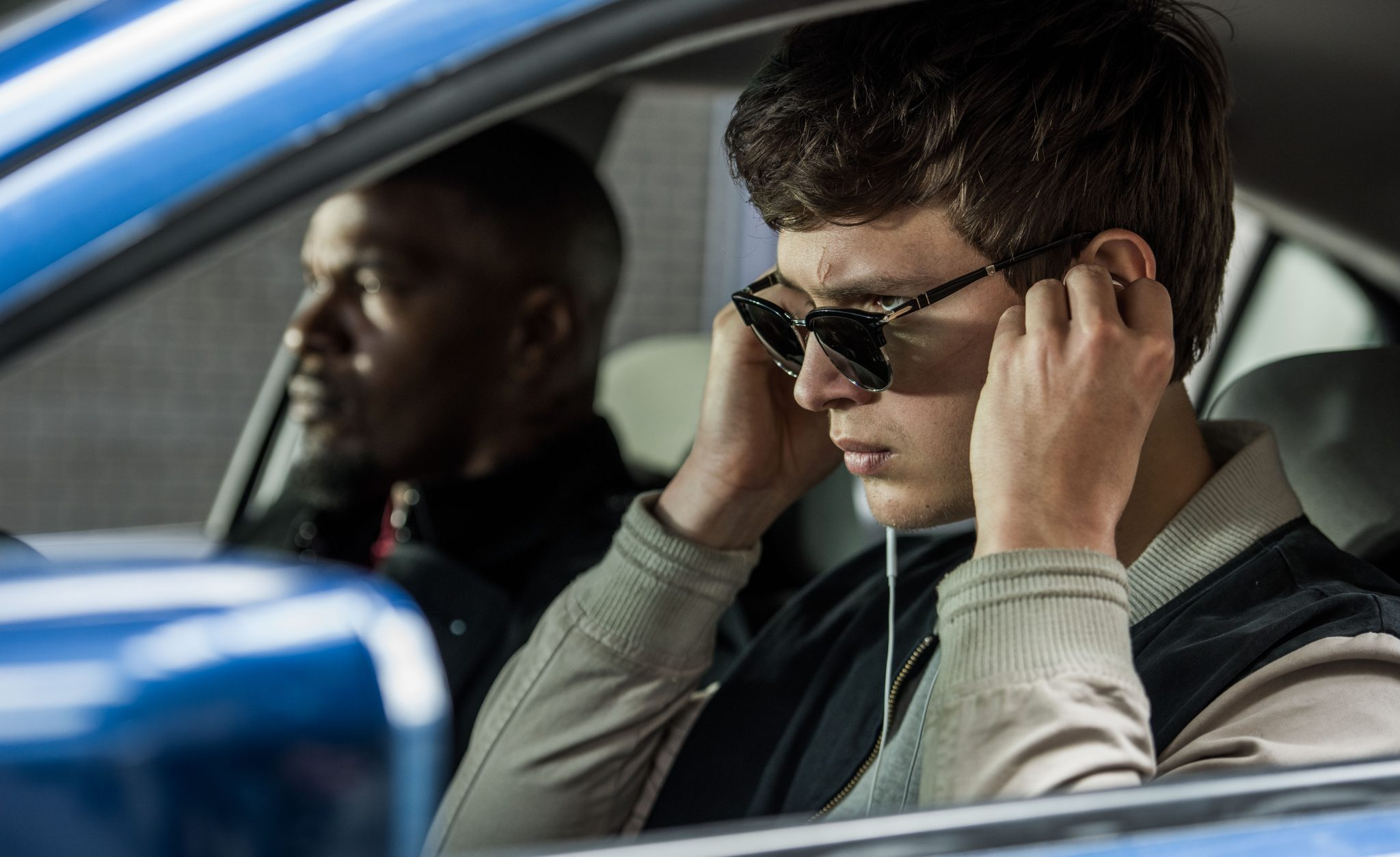 Baby (ANSEL ELGORT) and Bats (JAMIE FOXX) on the way to the post office job with Buddy (JON HAMM) and Darling (EIZA GONZALEZ) as cops pull up next to them in TriStar Pictures